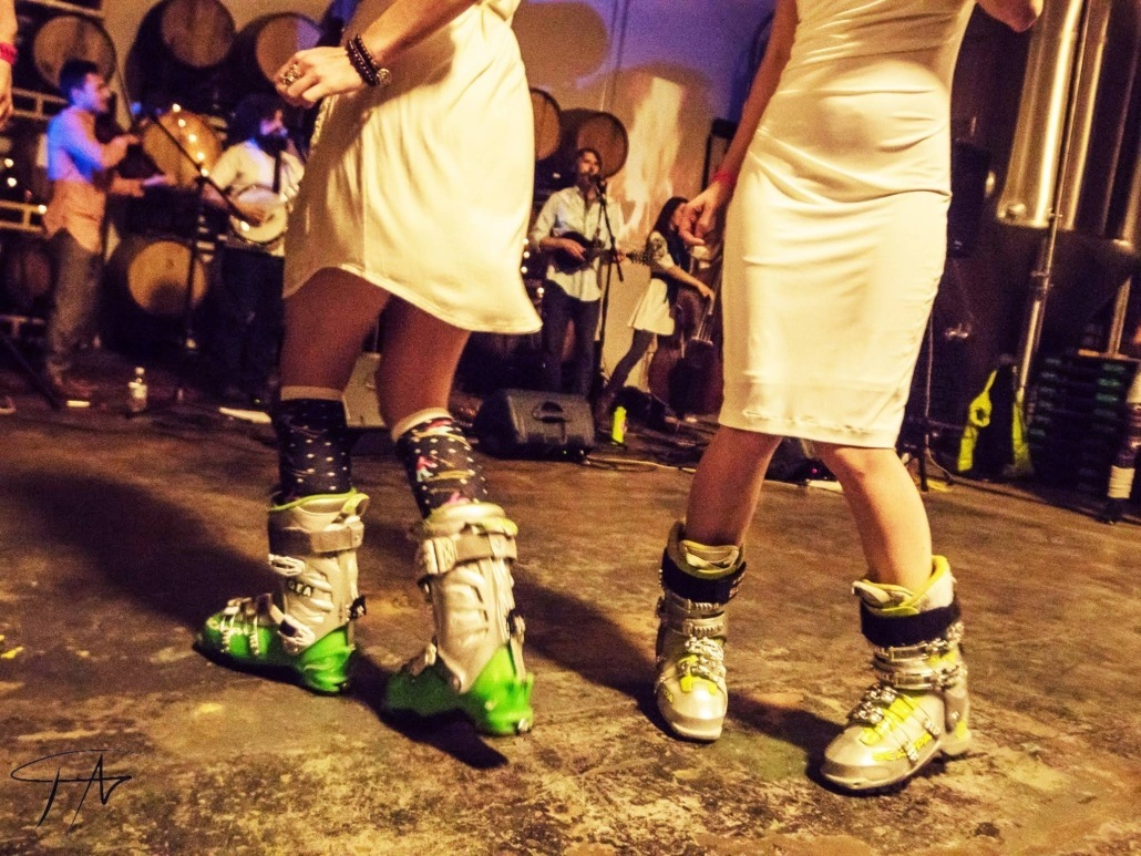 Two people in white skirts dance in ski boots during the snowball fundraiser for the snowschool