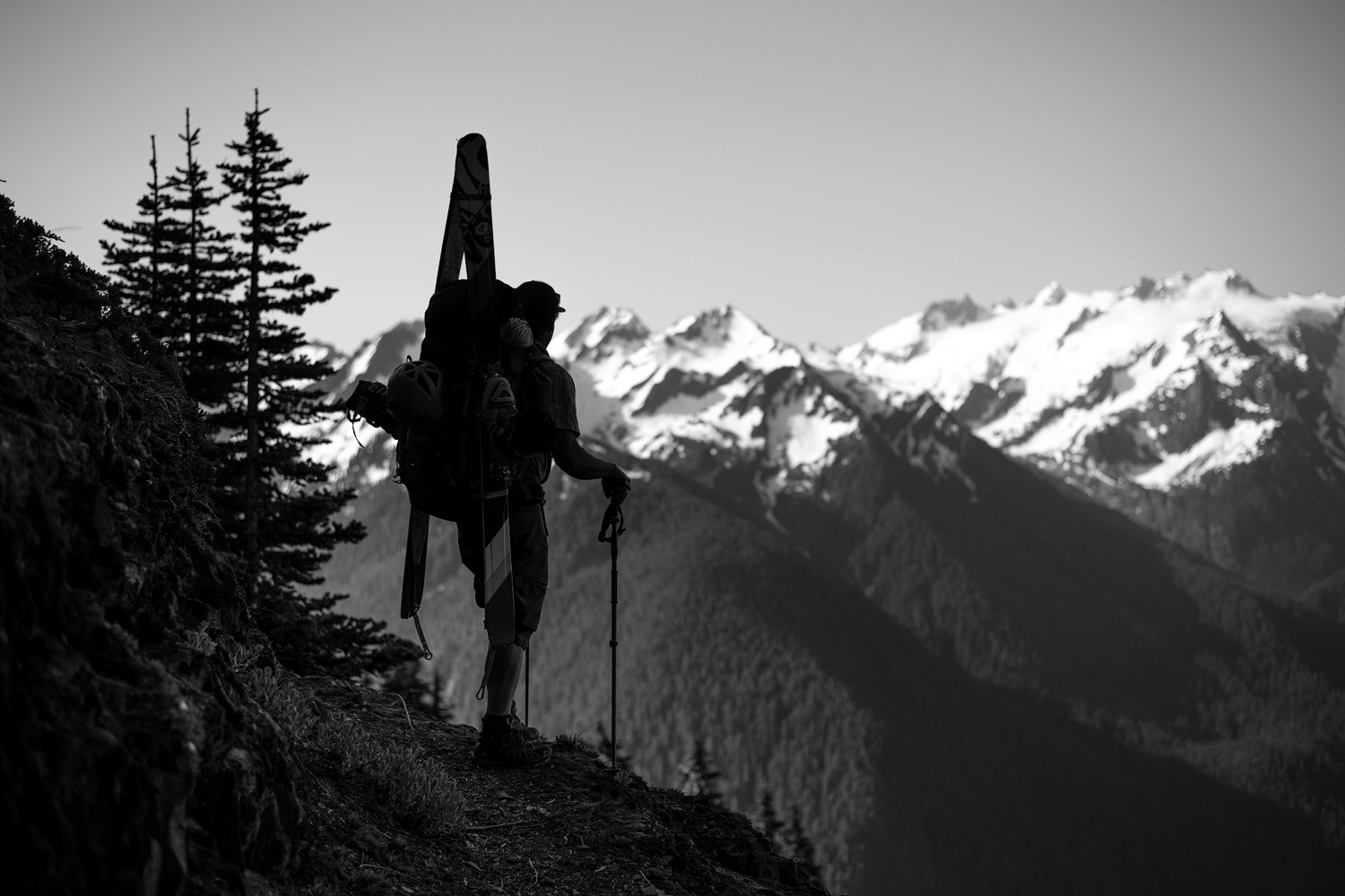A backcountry skier with his skis attached to his backpack stands on a ridgetop overlooking mountains in Washington's Olympic Peninsula