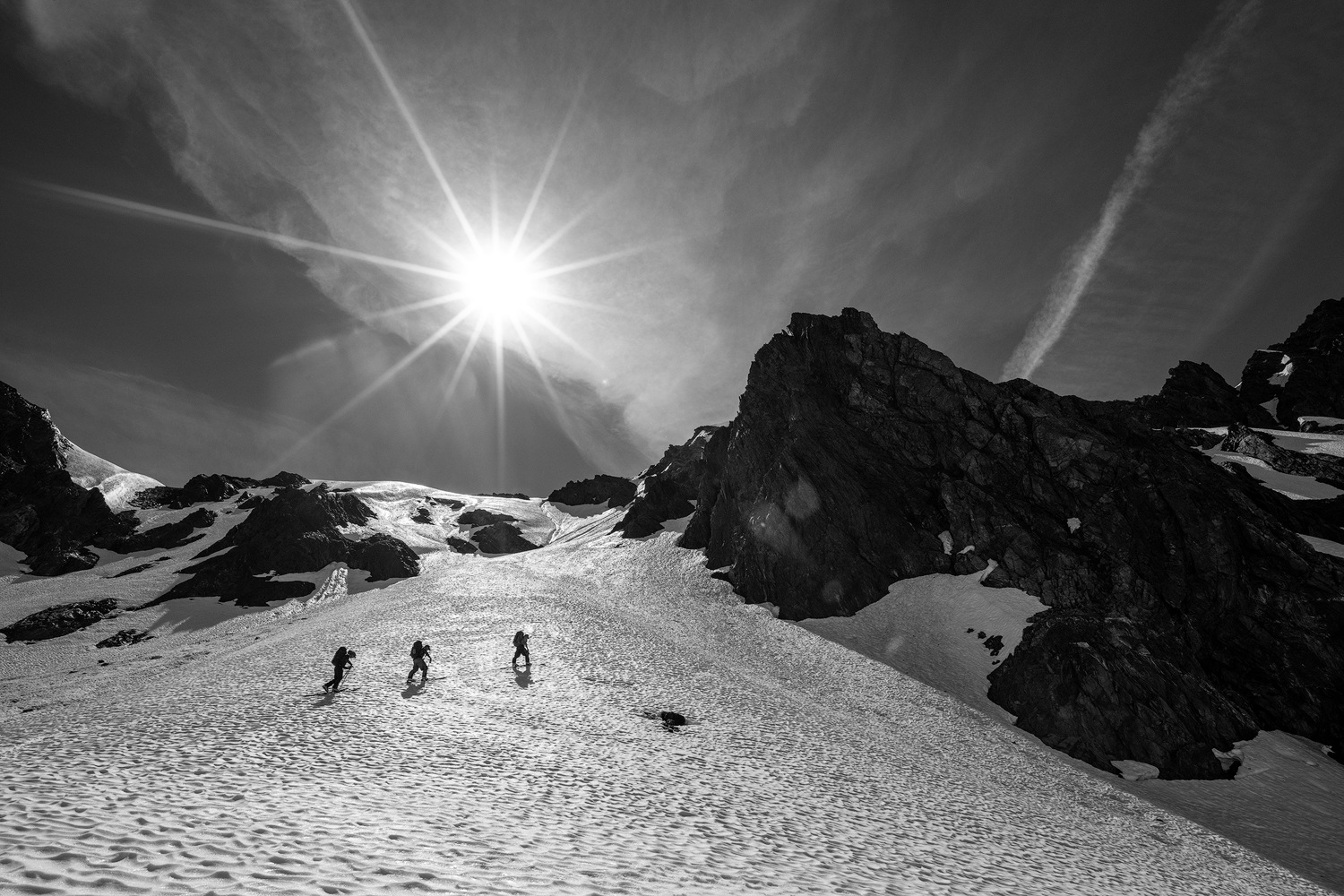 Several backcountry skiers skin across a glacier in Washington's Olympic Peninsula