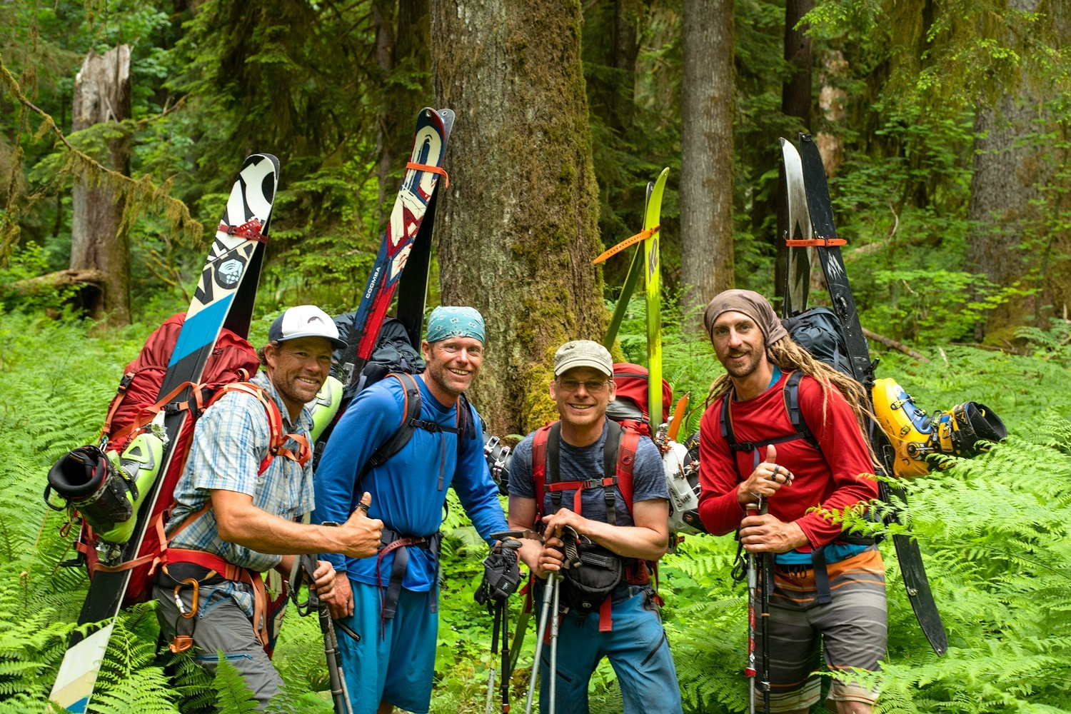 Four backcountry skiers on a mission to ski glaciers in Washington's Olympic Peninsula pose for a photo in the rainforest